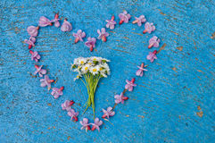 Heart shape formed from flowers on a blue background Stock Images