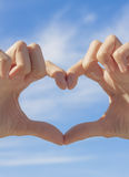 Heart shape formed by hands. On blue sky background Stock Photography