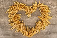 Heart shape of french fries isolated on concrete background. stock images