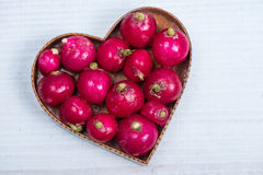 Heart shape with fresh radish. On white table Stock Photos