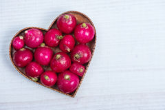 Heart shape with fresh radish. On white table Stock Photography