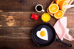 Heart shape fried egg, fresh orange juice and coffee. Top view Royalty Free Stock Images
