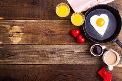 Heart shape fried egg, fresh orange juice and coffee. Top view Royalty Free Stock Photography