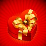 Heart shape gift with golden bow Stock Photos