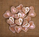 Heart shape gingerbread cookiesHeart shape gingerbread cookies. Decorated heart shape gingerbread cookies on burlap canvas background royalty free stock photography