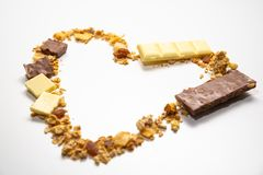 Heart shape from granola, muesli with dried banana, other fruits and white/ milk chocolate.  Side view. Healthy and balanced diet royalty free stock photography