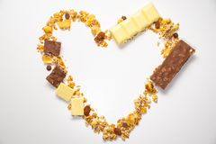 Heart shape from granola, muesli with dried banana, other fruits and white/ milk chocolate.  Top view. Healthy and balanced diet stock image