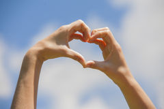 Heart shape hands. On the blue sky Royalty Free Stock Photo