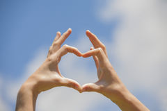 Heart shape hands. On the blue sky Royalty Free Stock Image
