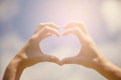 Heart shape hands. On the blue sky stock photos