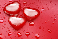 Heart shape ice. Three melting heart-shaped ice cubes over a red background Stock Photo