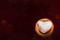 Heart shape ice on mini baked clay vase and dark red background Royalty Free Stock Photography