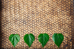 Heart shape leaf on bamboo mat Royalty Free Stock Photography