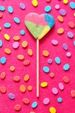 A heart shape lollipop displayed with colorful dots. On a oink background Stock Photography