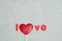 A heart shape lollipop replacing the letter o in the word love. On a white background Royalty Free Stock Images