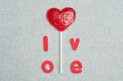 A heart shape lollipop with the word love. On a white background Royalty Free Stock Photo