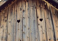 Heart shape look out on wooden old house. Love, bleached.. 103 years old. Heart shape in wooden abandoned house, rustic scene stock photography