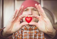 Heart shape love symbol in man hand with face on background Valentines Day Royalty Free Stock Images