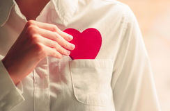Heart shape love symbol in woman hands. With white shirt pocket Valentines Day romantic greeting people relationship lifestyle feelings concept winter holiday stock images