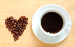 Heart shape made from coffee beans with cup of coffee Stock Photography