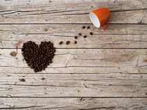 Heart shape made of coffee beans and cup on wooden background Stock Photos