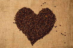 Heart shape made of coffee beans on linen cloth Royalty Free Stock Image