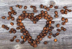 Heart shape made from coffee beans on wooden background Royalty Free Stock Image