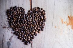 Heart shape made from coffee beans. On wooden backgrounds Royalty Free Stock Photos