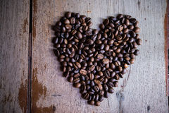 Heart shape made from coffee beans. On wooden backgrounds Stock Photos