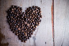 Heart shape made from coffee beans. On wooden backgrounds Royalty Free Stock Photo
