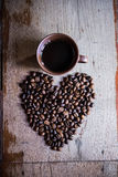 Heart shape made from coffee beans. On wooden backgrounds Royalty Free Stock Image