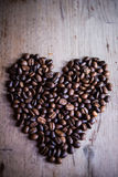 Heart shape made from coffee beans. On wooden backgrounds Stock Images