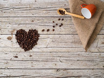 Heart shape made of coffee beans, wooden spoon and cup on wooden Stock Photography