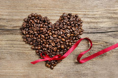 Heart shape made of coffee beans on wooden table royalty free stock image