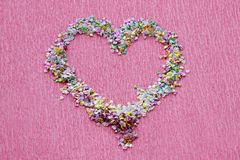 Heart shape of sequins, shimmer and confetti for manicure design on bright pink background. Heart shape made of colorful sequins, shimmer and confetti for Stock Images