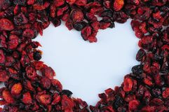 Heart shape made from dry cranberry fruits. On white background Stock Photos