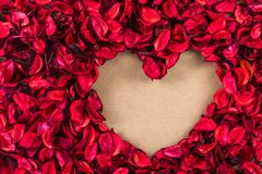 Heart shape made of dry petal. Heart shape made of red dry petal on craft paper, top view royalty free stock photo