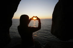 Heart shape made with a girl hands. At sunset stock photos