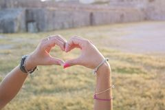 Heart shape made of girls hands in an old fortres Stock Photography
