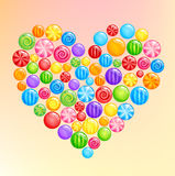 Heart shape made of glossy sweet candies lollipops multicolor Stock Images