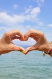 Heart shape made of hands against sea and sky Royalty Free Stock Photos