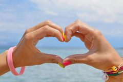 Heart shape made of hands against sea and sky Royalty Free Stock Photography