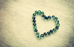 Heart shape made from marbles with vintage effect. valentines day concept or wedding concept. room for text. Stock Photos
