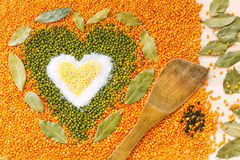 Heart shape made of mixed yellow wheat grains, white salt, green Stock Images