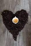 Heart shape made out of coffee beans on top of a table with an espresso cup in the middle Royalty Free Stock Images