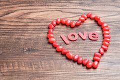 A heart shape made out of red jelly beans and the word love. On a wooden background Stock Photography