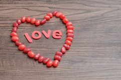 A heart shape made out of red jelly beans and the word love. On a wooden background Royalty Free Stock Photos