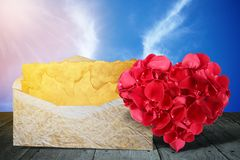 Heart shape made out of rose petals with old letter on wooden deck table stock images