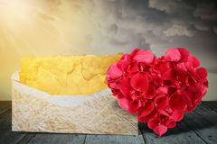 Heart shape made out of rose petals with old letter on wooden deck table stock image