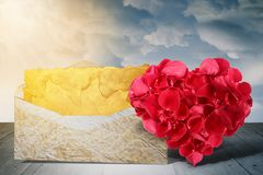 Heart shape made out of rose petals with old letter on wooden deck table stock photography